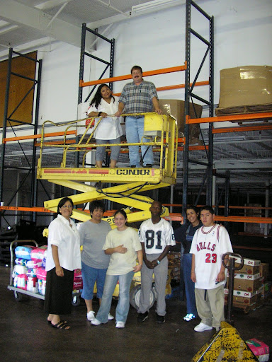 Staff and volunteers use the scissor lift to organize the warehouse