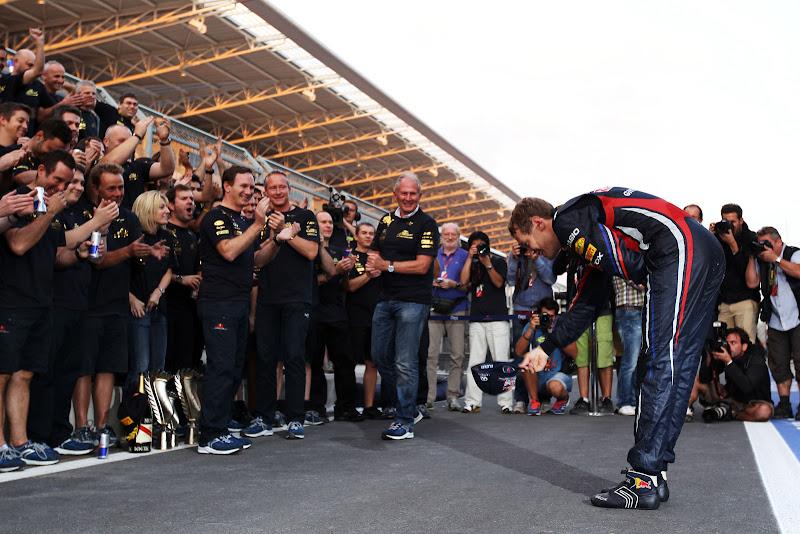 Себастьян Феттель пснимает кепку и кланяется перед своей командой Red Bull после победы в гонке на Гран-при Кореи 2011