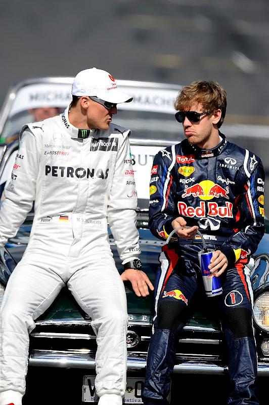 Михаэль Шумахер и Себастьян Феттель обсуждают что-то на фотосессии чемпионов на Гран-при Австралии 2012