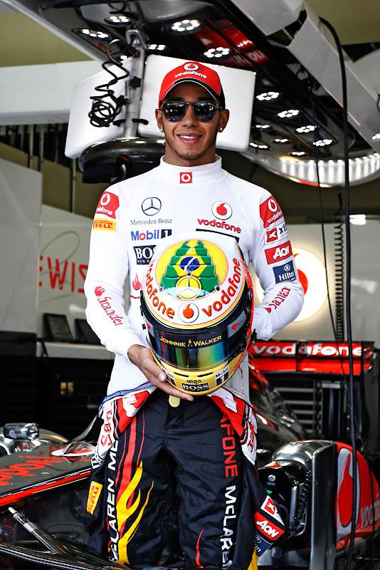 Льюис Хэмилтон демонстрирует шлем с бразильским флагом в память об Айртоне Сенне на Гран-при Бразилии 2011