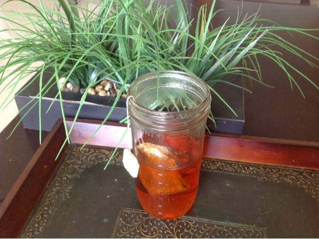 Mason jar of orange colored tea with tea bag