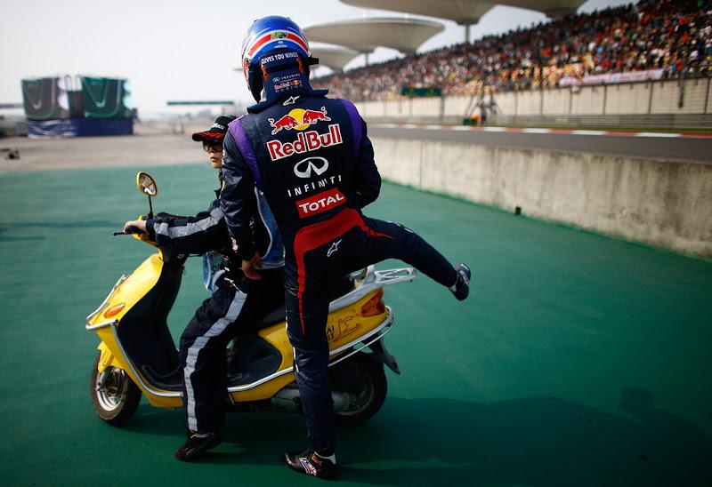 Марк Уэббер садится на мопед после схода с Гран-при Китая 2013