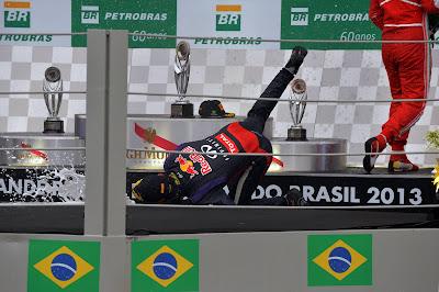 Марк Уэббер падает с бутылкой шампанского на подиуме Гран-при Бразилии 2013