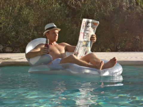 Нико Росберг в шляпе в бассейне с газетой перед гонкой в Спа