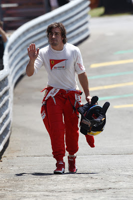 Фернандо Алонсо приветствует болельщиков после схода во во время первой сессии свободных заездов на Гран-при Бразилии 2011