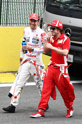 веселые и улыбающиеся Дженсон Баттон и Фернандо Алонсо идут по трассе на Гран-при Бразилии 2011