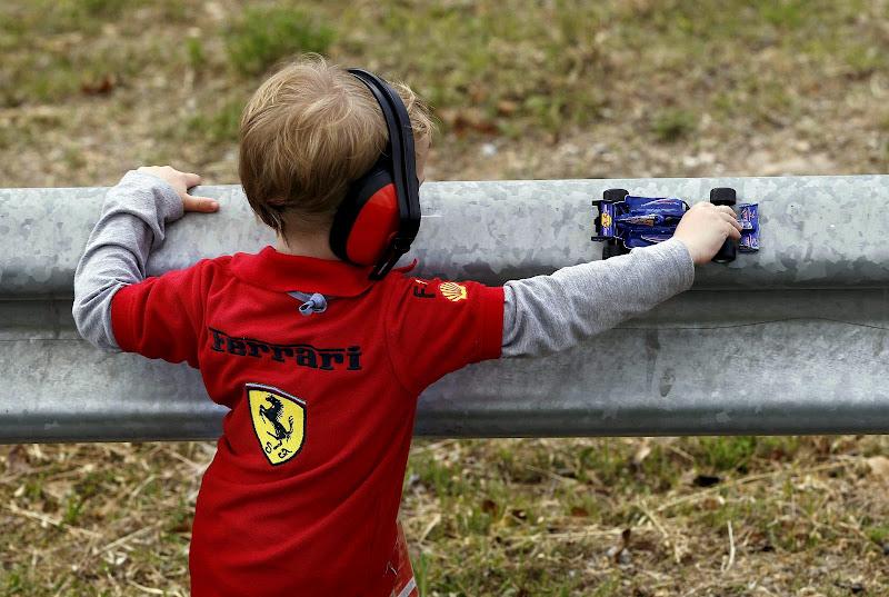 ребенок в футболке Ferrari с болидом Red Bull на Гран-при Испании 2013