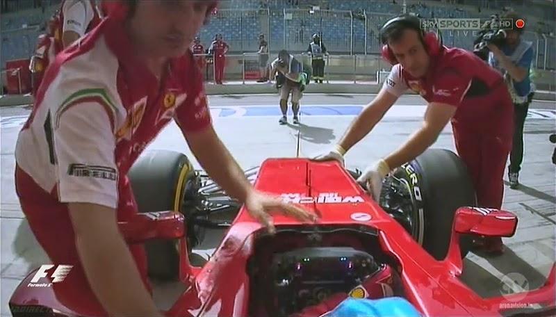 механики Ferrari закатывают болид Фернандо Алонсо в боксы во время первой сессии свободных заездов на Гран-при Бахрейна 2014