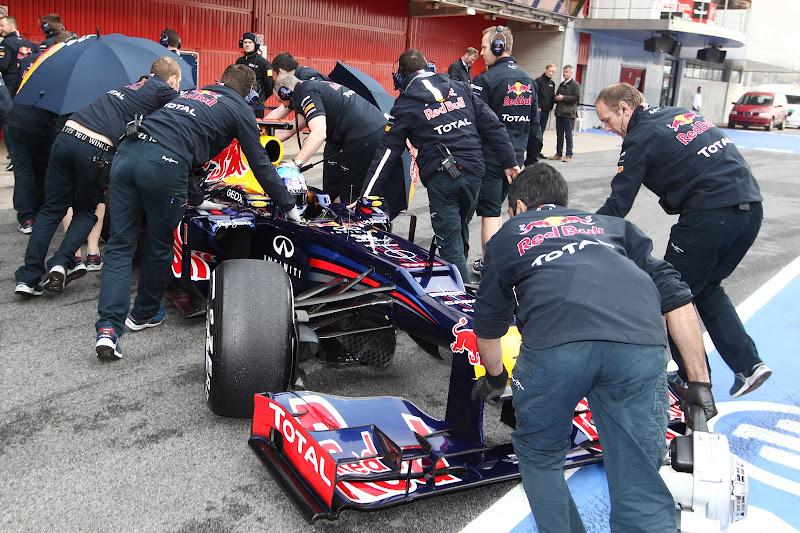 механики Red Bull спешно закатывают болид Себастьяна Феттеля в гараж после заездов на трассе Каталунья на предсезонных тестах 2012 в Барселоне 4 марта 2012