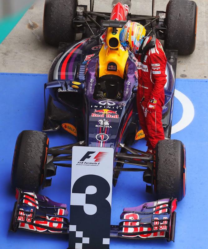 Фернандо Алонсо разглядывает болид Red Bull после финиша Гран-при Малайзии 2014