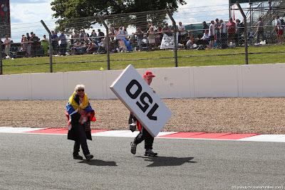 болельщик несет отметку 150 от поворота на Гран-при Великобритании 2014