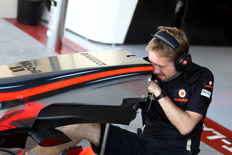 механик McLaren заглядывает в переднее антикрыло на молодежных тестах в Абу-Даби 2011