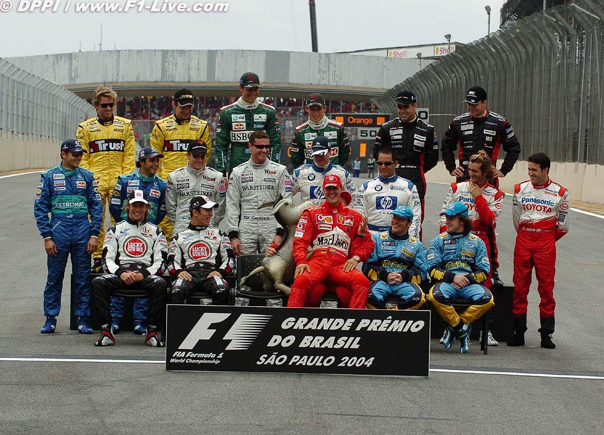 Михаэль Шумахер на коленях у Рубенса Баррикелло на Гран-при Бразилии 2004