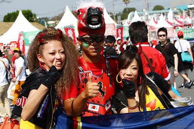 болельщицы Себастьяна Феттеля и Red Bull фотографируются с болельщиком Ferrari на Гран-при Японии 2011