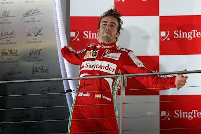 Фернандо Алонсо растягивает спину на подиуме Гран-при Сингапура 2013
