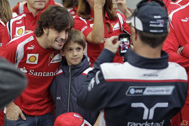 Рубенс Баррикелло фотографирует на телефон своего сына Эдуардо с Фернандо Алонсо на Гран-при Бразилии 2011