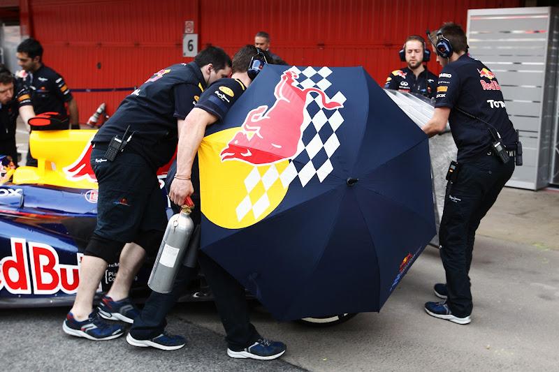 механики Red Bull зарывают болид Себастьяна Феттеля зонтиками от фотографов на предсезонных тестах 2012 в Барселоне 4 марта 2012