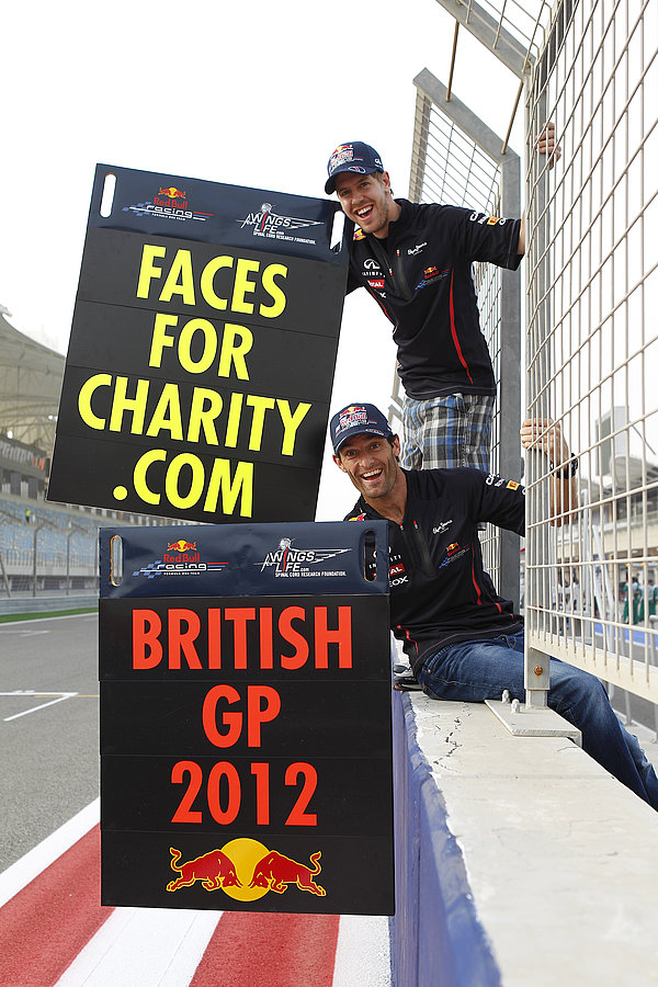 Себастьян Феттель и Марк Уэббер на пит-лейне с табличками Faces For Charity .com British GP 2012