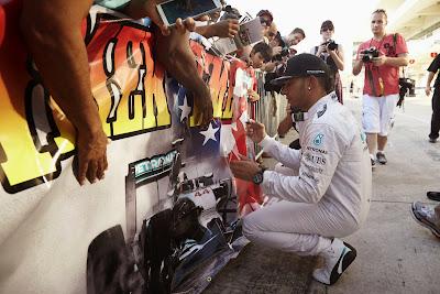 Льюис Хэмилтон ставит автограф на баннере болельщиков Гран-при США 2014