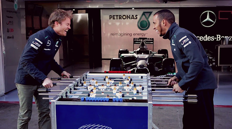 Нико Росберг и Льюис Хэмилтон играю в настольный футбол на съемках для Allianz перед Гран-при Австралии 2013