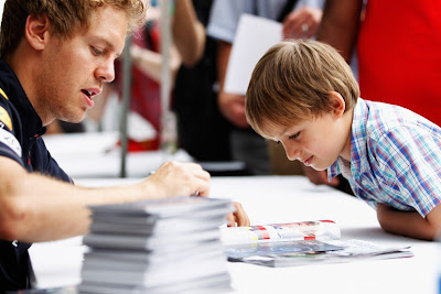 мальчик рассматривает автограф Себастьяна Феттеля на Гран-при Канады 2011