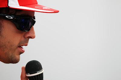 Фернандо Алонсо держит микрофон во время интервью на Гран-при Сингапура 2011