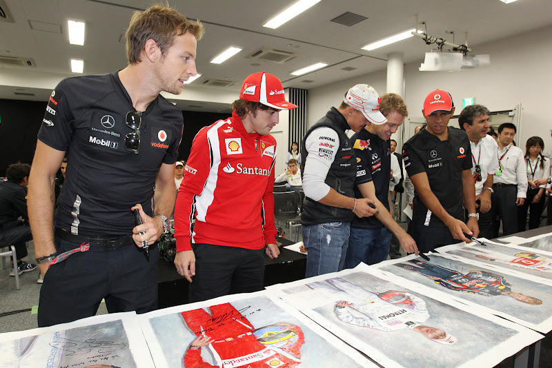 пилоты рассматривают постеры со своими автографами на Гран-при Японии 2011