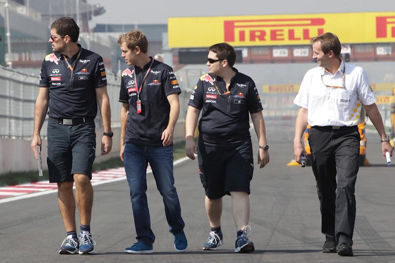 Себастьян Феттель со своими механиками смотрят в сторону во время прогулки по треку Йонама на Гран-при Кореи 2011