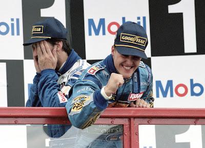 Деймон Хилл фэйспалмит на фоне празднующего победу Михаэля Шумахера на подиуме Гран-при Франции 1995