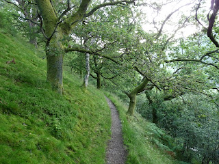Walking on the narrow path heading away from Bridge End around the base of High Rigg.
