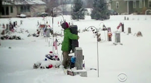 Eight-year-old Myles Eckert hugs the grave of his dad, Army Sergeant Andy Eckert. (Screenshot YouTube / CBS News)