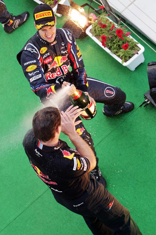 Себастьян Феттель поливает Кристиана Хорнера шампанским на подиуме Гран-при Кореи 2011