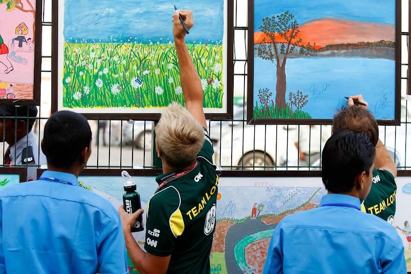Ярно Трулли и Хейкки Ковалайнен ставят автографы на рисунках индийских школьников на Гран-при Индии 2011