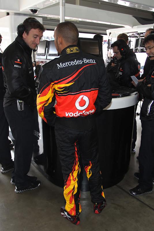 Льюис Хэмилтон с механиками McLaren в гараже команды во время квалификации в специально подготовленном для Гран-при Германии 2011 комбинезоне от Hugo Boss