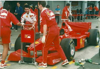 механики Ferrari прячут крылья болида красными чехлами на Гран-при Великобритании 1998