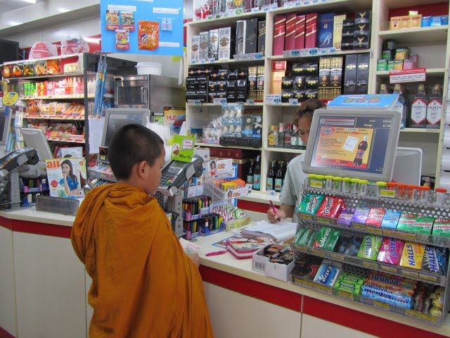 little monk buying a manga at a 7Eleven at Khao San road, Bangkok