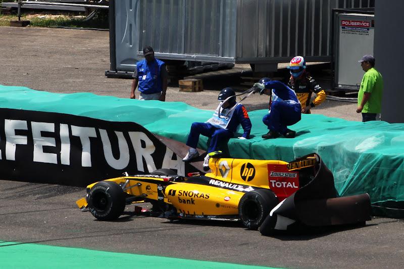 маршалы пробираются к разбитому болиду Renault Виталия Петрова на Гран-при Бразилии 2010