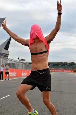 Дженсон Баттон в розовой футболке бежит по трассе Сильверстоуна на Гран-при Великобритании 2014