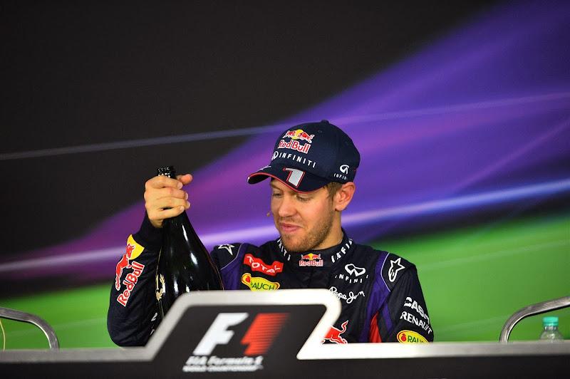 Себастьян Феттель достает бутылку шампанского на пресс-конференции после гонки на Гран-при Индии 2013