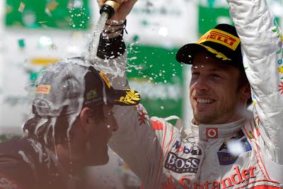 Дженсон Баттон обливает Марка Уэббера шампанским на подиуме Гран-при Бразилии 2011