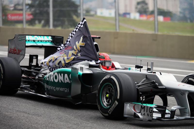 Михаэль Шумахер с флагом на трассе Интерлагос на Гран-при Бразилии 2012