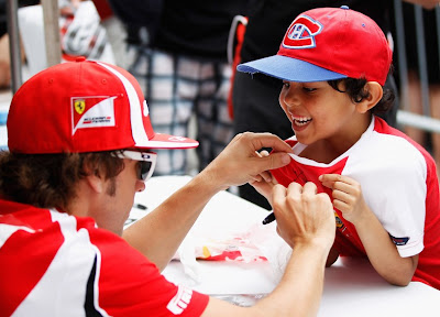 Фернандо Алонсо дает автограф мальчику на Гран-при Канады 2011