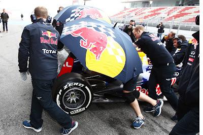 механики Red Bull зарывают болид Себастьяна Феттеля зонтиками от фотографов на предсезонных тестах 2012 в Барселоне 4 марта 2012 umbrella defense