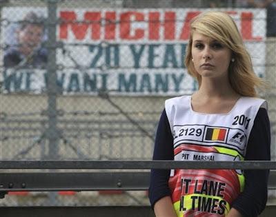 девушка маршал на пит-лейне на фоне плаката Шумахера Гран-при Бельгии 2011 в Спа-Франкошам