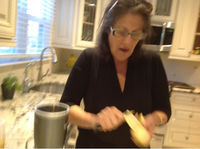 woman peeling a plantain in her kitchen