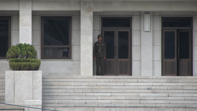 The North Korean DPRK soldiers. Notice the one staring back at us through the window.