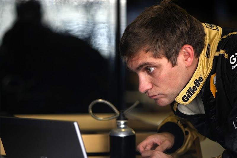 Виталий Петров смотрит в ноутбук на Гран-при Абу-Даби 2011