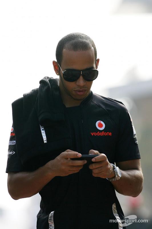 Льюис Хэмилтон пишет что-то на своем телефоне на Гран-при Кореи 2011