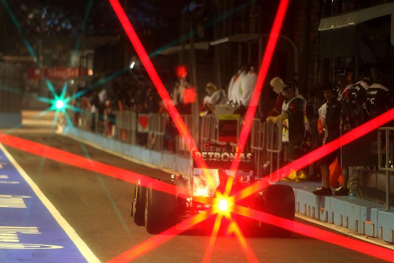 болид Mercedes GP едет по пит-лейну с красным огоньком позади на Гран-при Сингапура 2011