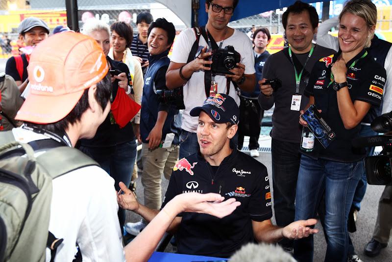 Себастьян Феттель разводит руками перед болельщиком McLaren на автограф-сессии Гран-при Японии 2011